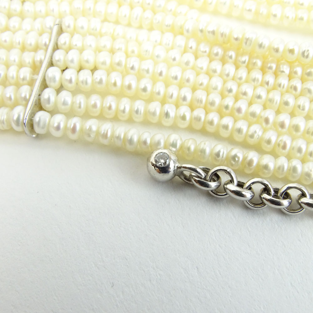 18 Karat White Gold and 10 Strand White Pearl Choker Necklace accented with small round cut diamonds.