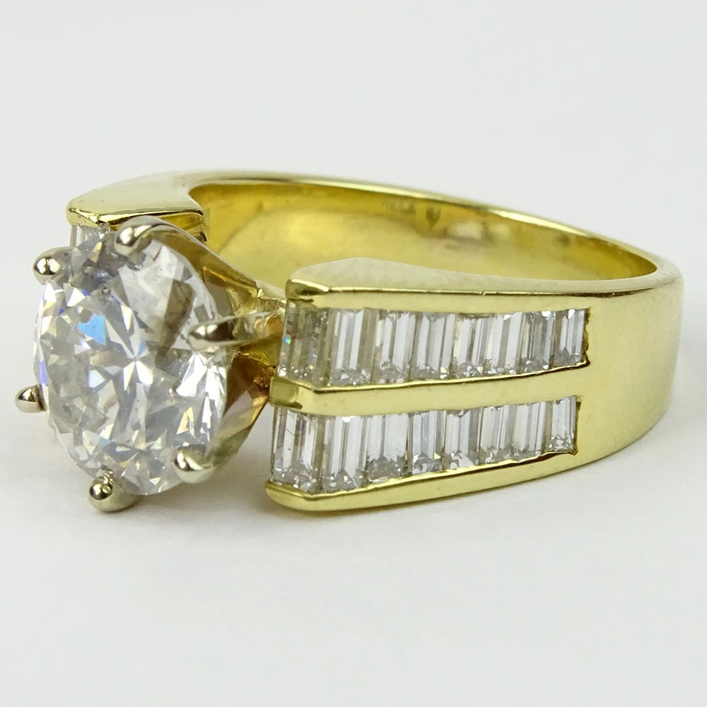 Approx. 2.45 Carat Round Brilliant Cut Diamond and 18 Karat Yellow Gold Engagement Ring Accented with .50 Carat Baguette Cut Diamonds.
