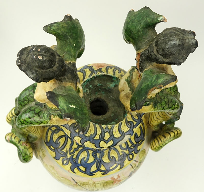 19th Century Italian Faience Majolica Renaissance Style Pottery Urn. Decorated with winged nude figural handles above figural idols, yellow ground with intertwining patterns.