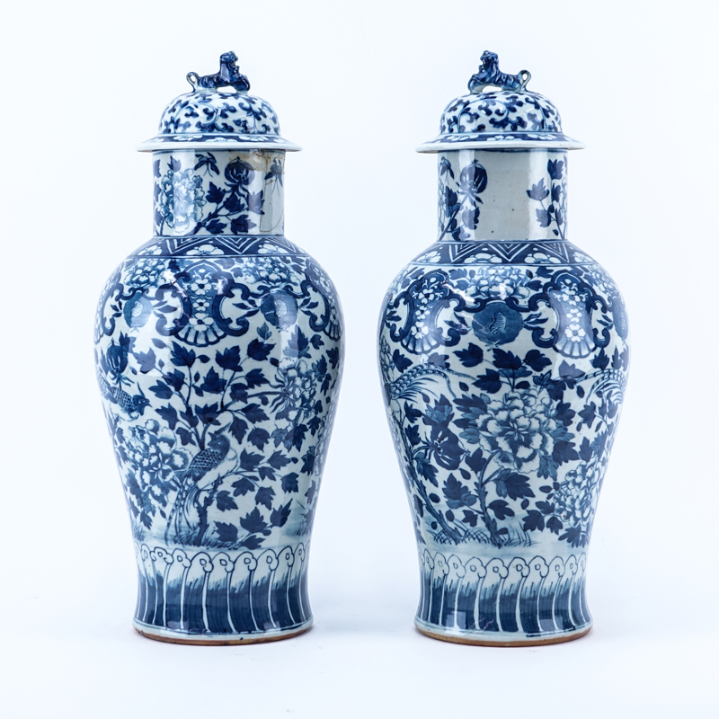 Pair of Mid Century Chinese Blue and White Porcelain Covered Urns with Foo Dog Finial.