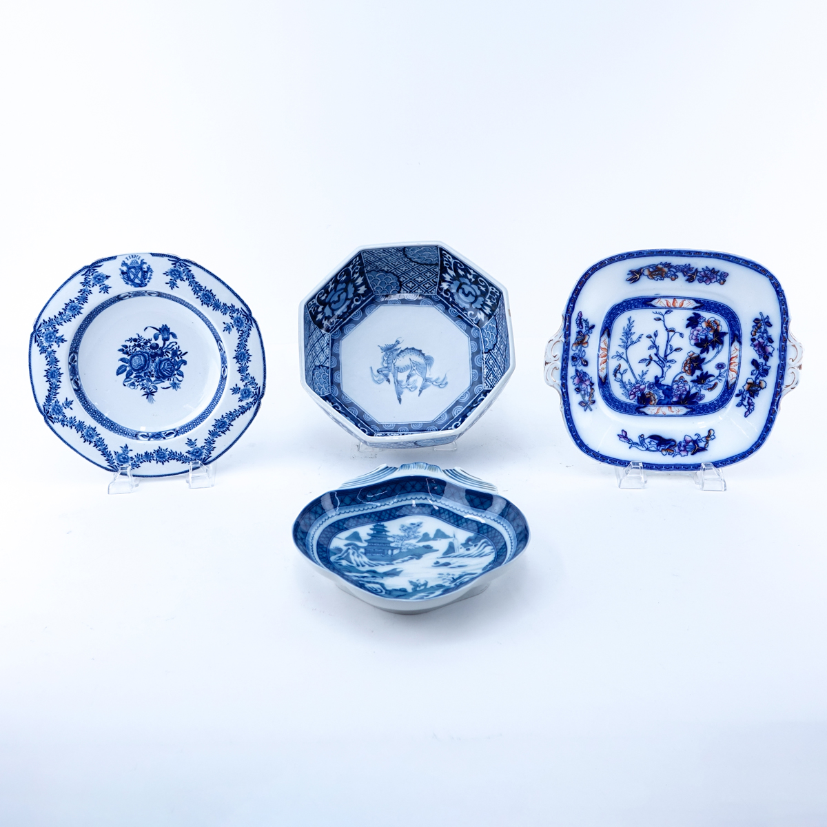 Four Pieces Blue & White Pottery Decorative Table Top Items. Includes a Mottahedeh Chinese motif dish, a flow blue platter, a Chinese bowl and an unsigned dish.
