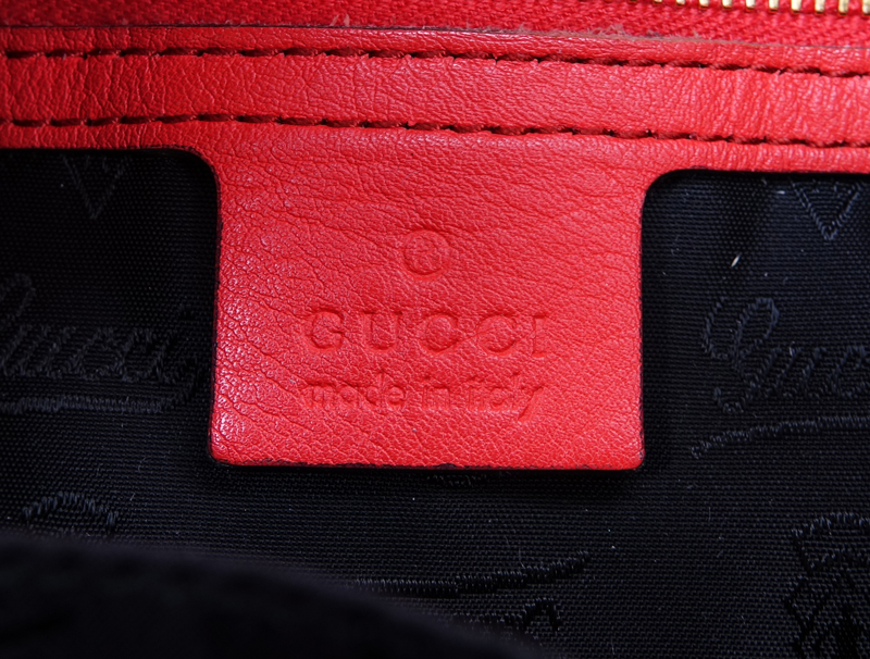 Gucci Orange Leather New Jackie Indy Handbag. Gold tone hardware, black signature fabric interior with zippered and patch pockets.