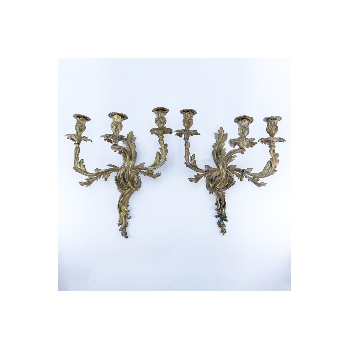 Pair of French Louis XV/Rococo Style Three Arm Gilt Bronze Wall Sconces. One has been professionall