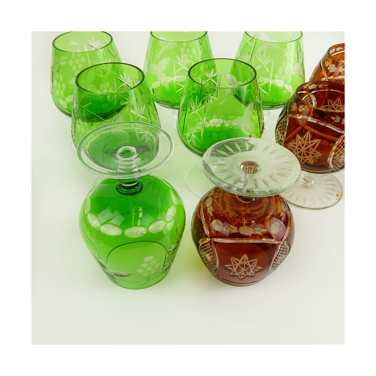 Lot of 9 Bohemian Cut Glass Brandy glasses in Green and Deep Orange. Various stems. Measure 4-1/2""